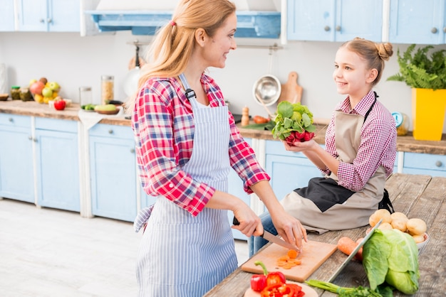 Mãe e filha olhando uns aos outros enquanto prepara a comida na cozinha