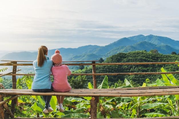 Mãe e filha olhavam para a montanha.