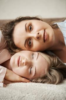 Mãe e filha parecendo melhores amigas. tiro vertical da jovem mulher atraente, deitado na cabeça de outra garota e sorrindo com expressão relaxada e calma, sentindo-se feliz