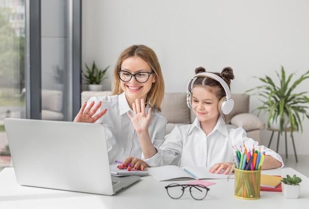 Mãe e filha participando de uma aula on-line