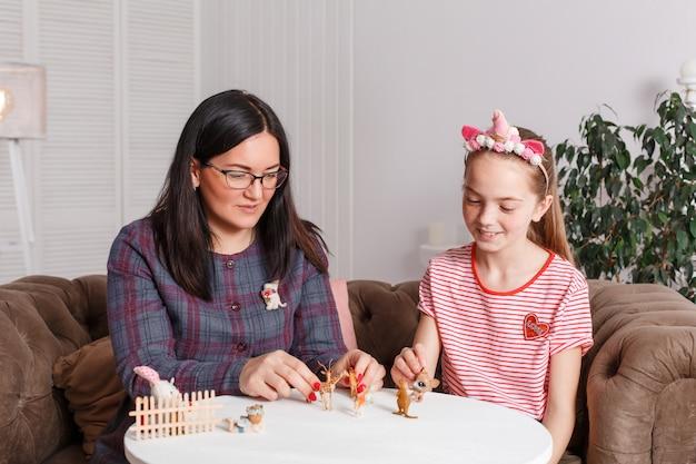 Mãe e filha passam tempo juntos, sentam no sofá, conversando e brincando com animais de brinquedo. mães e filhas de lazer