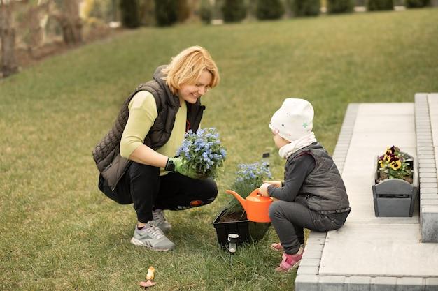 Mãe e filha passam um tempo juntas na frente ou no quintal da casa plantando flores