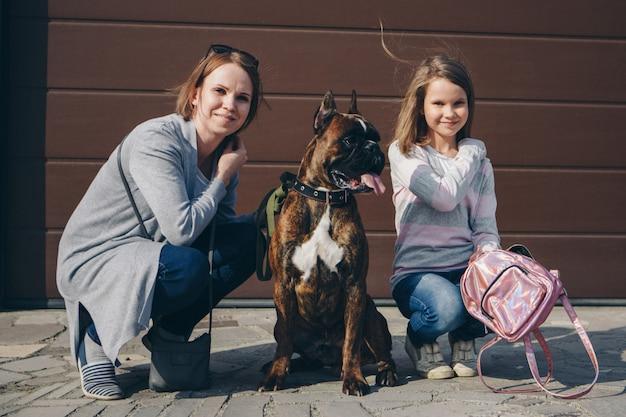 Mãe e filha passeando com seu cachorro