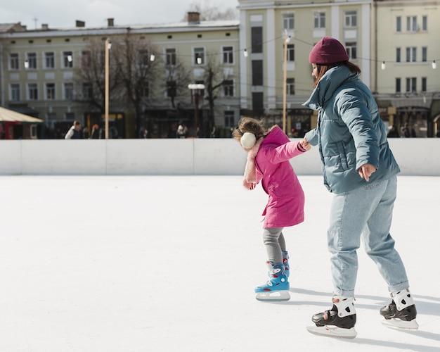Mãe e filha patinando juntos