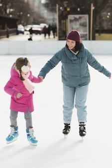 Mãe e filha patinando no gelo