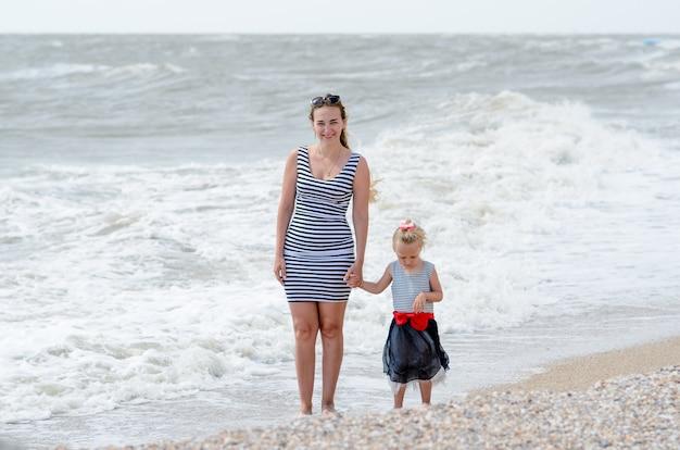 Mãe e filha pequena descansando na costa do mar.
