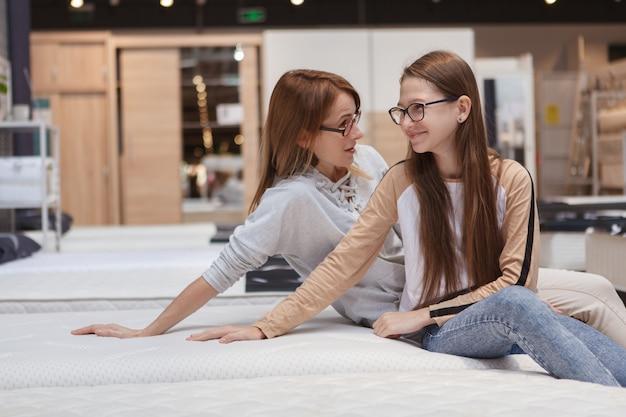Mãe e filha pequena sentada em uma cama ortopédica nova em uma loja de móveis, copie o espaço