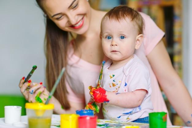 Mãe e filha pintam sobre tela na escola de desenho