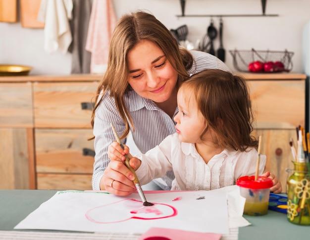 Mãe e filha pintando coração no papel