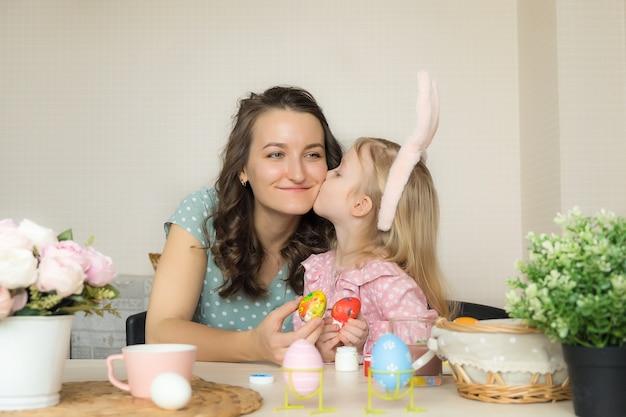 Mãe e filha pintando ovos para a páscoa