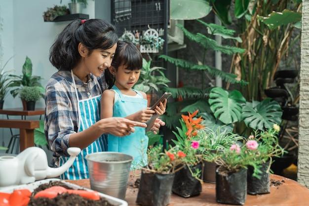 Mãe e filha plantando flores juntos