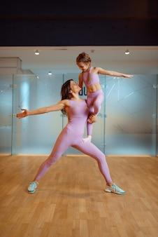 Mãe e filha posam no ginásio, estilo de vida saudável, treino de fitness. mãe e filha em roupas esportivas, mulher com filho em treinamento conjunto no clube de esporte