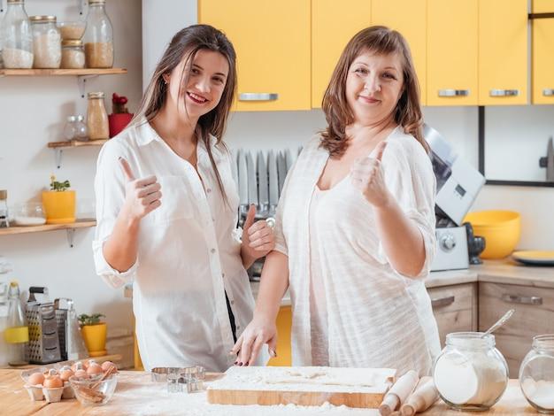 Mãe e filha posando na cozinha da família