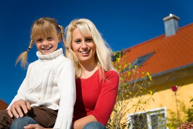Mãe e filha posando na frente de uma casa