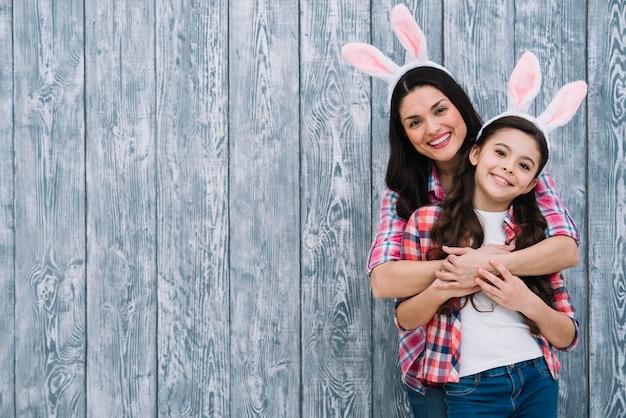 Mãe e filha posando na frente do pano de fundo cinza de madeira