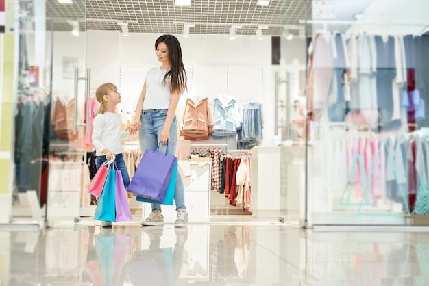 Mãe e filha posando perto de boutique com sacolas de compras.