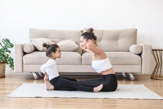 Mãe e filha praticam esportes em casa perto do sofá