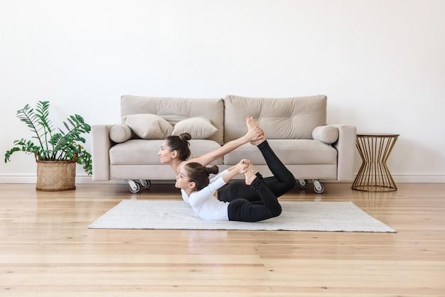 Mãe e filha praticam esportes praticando ioga, alongamento em casa