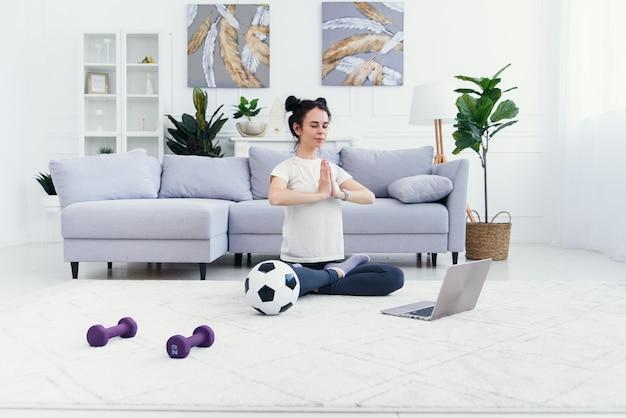 Mãe e filha praticando aula de ioga on-line em casa no período de isolamento de quarentena durante a pandemia de coronavírus. família fazendo esporte juntos on-line em casa. estilo de vida saudável