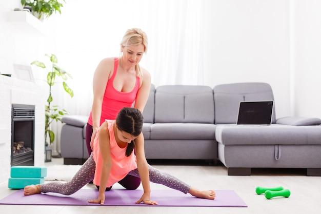 Mãe e filha praticando aula de ioga on-line em casa