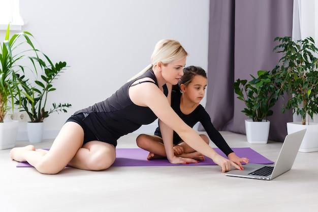 Mãe e filha praticando aula de ioga online em casa no período de isolamento de quarentena durante a pandemia de coronavírus. família fazendo esportes online em casa. estilo de vida saudável