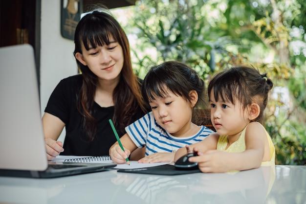 Mãe e filha pré-escolar usando o laptop para estudar em casa.