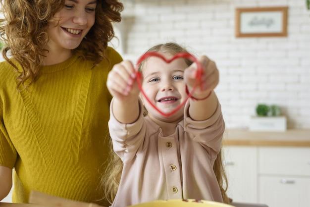 Mãe e filha preparam bolo juntas na cozinha