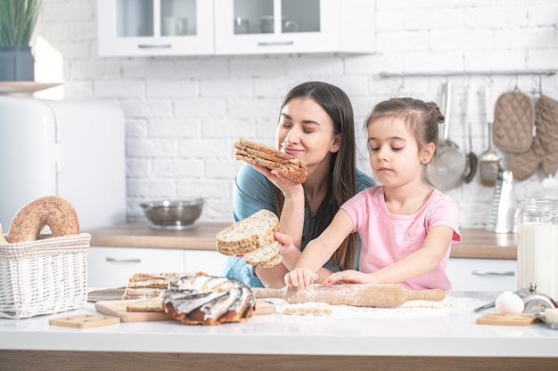 Mãe e filha preparam bolos na cozinha.