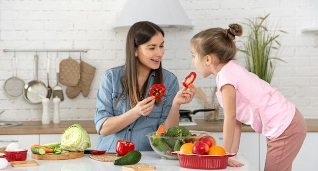 Mãe e filha preparam uma salada na cozinha. divirta-se e brinque com vegetais