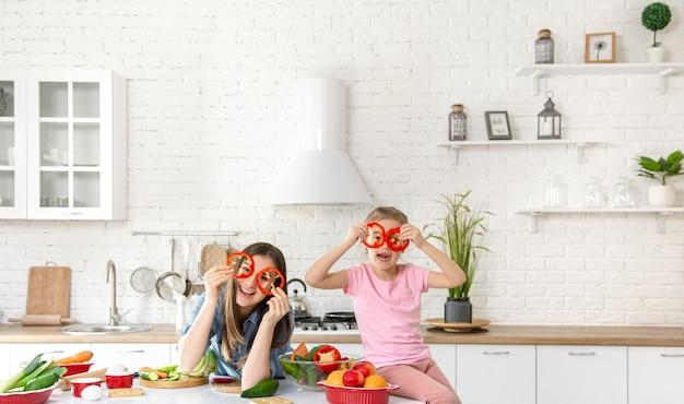 Mãe e filha preparam uma salada na cozinha.
