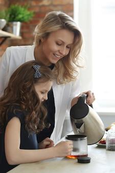 Mãe e filha preparando café ou chá