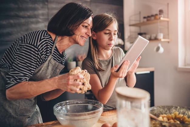 Mãe e filha procurando receita de torta de maçã no tablet