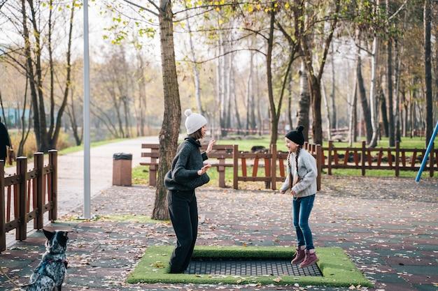 Mãe e filha pulando juntos na cama elástica no parque outono