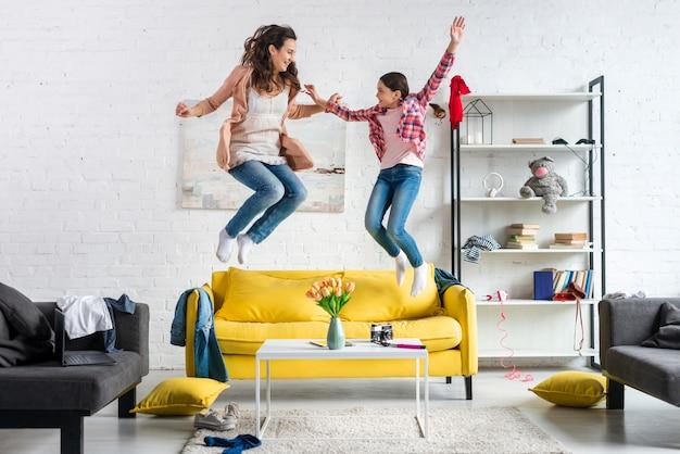 Mãe e filha pulando na sala de estar