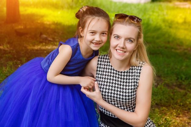 Mãe e filha que abraçam no amor que joga no parque.
