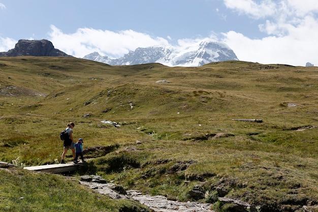 Mãe e filha que caminham nas montanhas alpinas perto de sunnega em suíça.