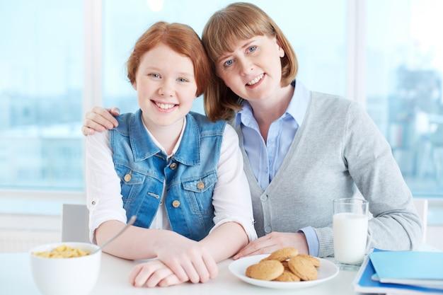 Mãe e filha que comem o pequeno almoço na cozinha
