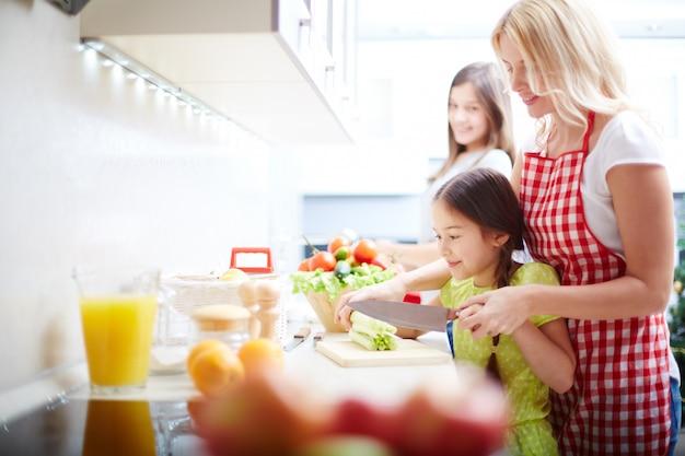 Mãe e filha que cozinham na cozinha