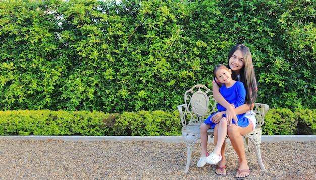 Mãe e filha que sentam-se junto na cadeira luxuosa do estilo de europa no jardim.