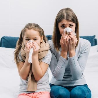 Mãe e filha que sofrem de frio e febre, cobrindo o nariz com lenço de papel