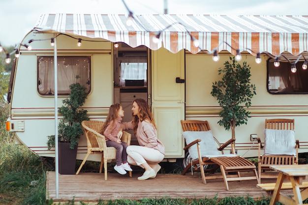 Mãe e filha relaxando e se divertindo no campo em férias de van campista