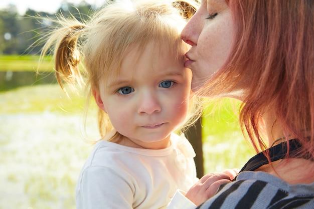 Mãe e filha retrato abraço beijando no parque