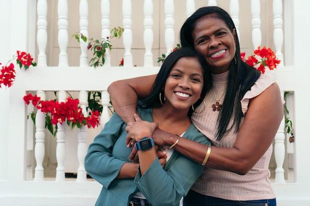 Mãe e filha rindo em um abraço ao ar livre