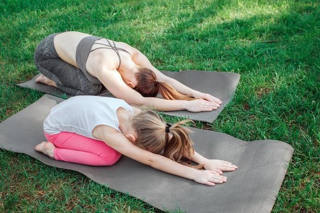 Mãe e filha são relaxantes. também eles curvaram seus corpos e se esticaram dessa maneira. garotas estão olhando para baixo.