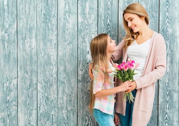 Mãe e filha satisfeita sorrindo e olhando para o outro