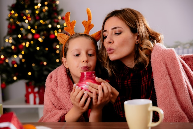 Mãe e filha satisfeitas com um cobertor segurando e soprando uma vela, sentadas à mesa, aproveitando o natal em casa