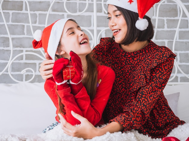 Mãe e filha se abraçam alegremente e comemoram o natal na cama