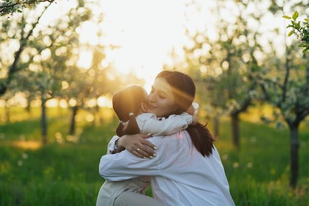 Mãe e filha se abraçando na natureza
