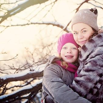 Mãe e filha se abraçando no dia de inverno ao ar livre. família feliz de inverno
