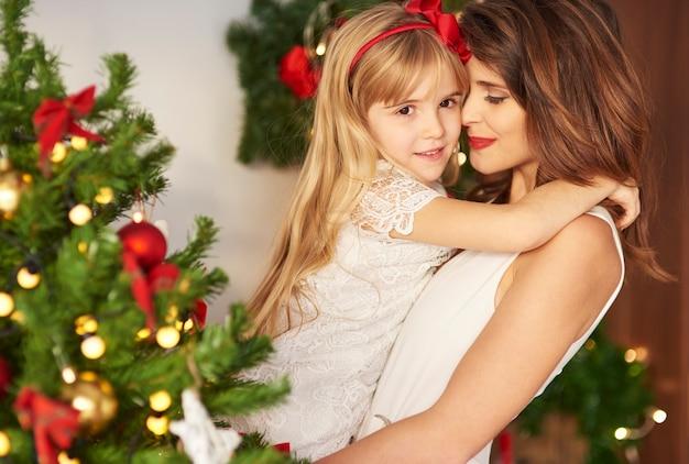 Mãe e filha se abraçando perto da árvore de natal